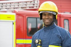 Fireman standing by fire engine wearing helmet - stock photo