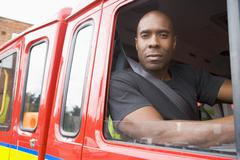 Fireman sitting in fire engine looking out window Stock Photos