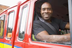 Fireman sitting in fire engine looking out window - stock photo