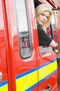 Firewoman sitting in fire engine with head out window - stock photo