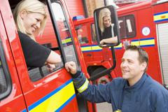 Firewoman sitting in fire engine talking to fireman standing outside Stock Photos