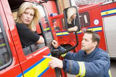 Fireman pointing something out to firewoman sitting in fire engine - stock photo