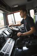 Fireman in fire engine holding steering wheel Stock Photos