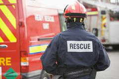 Rescue worker walking back to rescue vehicle - stock photo