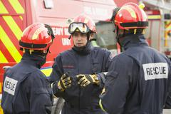 Three rescue workers talking by rescue vehicle Stock Photos