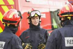 Stock Photo of Three rescue workers talking by rescue vehicle