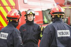 Three rescue workers talking by rescue vehicle (selective focus) - stock photo