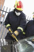 Two firefighters cutting out a windshield after an accident - stock photo
