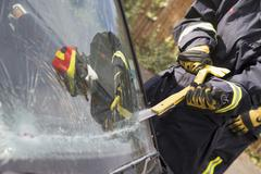 Firefighter cutting out a windshield after an accident Stock Photos