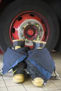Firefighting uniform on floor by fire engine Stock Photos