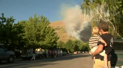 Families watch forest fire burning near neighborhood Stock Footage
