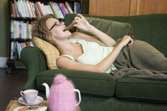Young woman lying on sofa at home eating chocolate Stock Photos