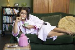 Young woman lying on sofa at home eating cookies and drinking tea Stock Photos