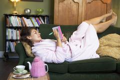 Young woman lying on sofa at home writing in her diary Stock Photos