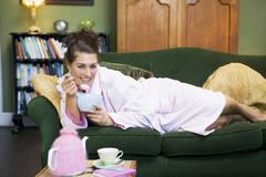 Young woman lying on sofa at home eating a sweet treat Stock Photos