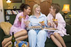 Three woman in night clothes sitting at home eating pizza - stock photo