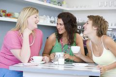 Three young woman sitting at a table and drinking tea Stock Photos