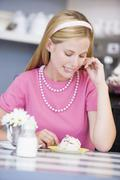 Young woman sitting at a table eating a sweet treat Stock Photos