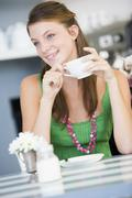 Young woman sitting at a table drinking tea Stock Photos