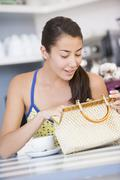 Young woman sitting at a table checking her handbag Stock Photos