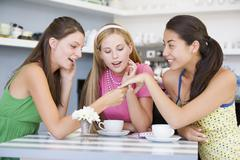 Young woman showing off engagement ring to friends - stock photo