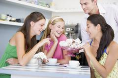 Man offering sweet treats to three young women - stock photo