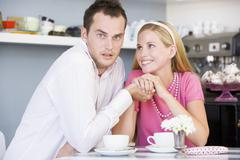 Young couple sitting at a table and having tea together Stock Photos