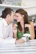 Young couple sitting at a table looking into each other's eyes Stock Photos