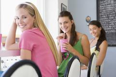 Three young women having a cold drink in a cafeteria - stock photo