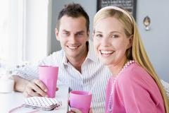 Young couple having a cold drink in a cafeteria Stock Photos