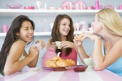 Three young woman sitting at a table having tea and a snack - stock photo