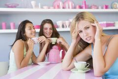 Young woman with a hangover sitting at a table with two friends Stock Photos