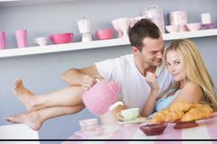 Young couple sitting at a table flirting and having tea Stock Photos
