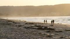 Ouples walk on beach at sunset Stock Footage