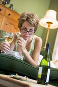 Young woman at home smoking and drinking wine by telephone Stock Photos