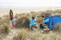 Young family relaxing on beach camping holiday Stock Photos