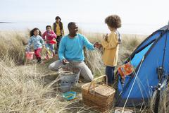 Stock Photo of young family relaxing on beach camping holiday