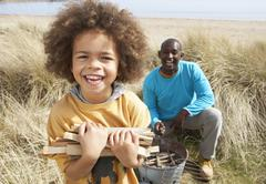 Stock Photo of father and son collecting firewood on beach camping holiday