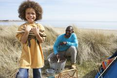 Father and son collecting firewood on beach camping holiday Stock Photos