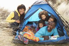 Young family relaxing inside tent on camping holiday Stock Photos