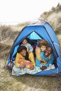 Stock Photo of young family relaxing inside tent on camping holiday