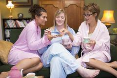 Three woman in night clothes sitting at home eating cookies and drinking tea Stock Photos