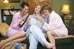 Three woman in night clothes sitting at home drinking wine - stock photo