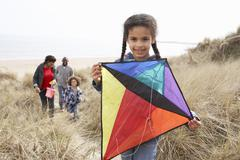 Family having fun with kite in sand dunes Stock Photos