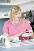 Young woman sitting at a table checking change purse Stock Photos
