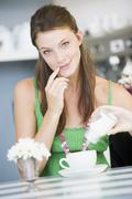Young woman sitting at a table drinking tea - stock photo