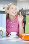 Young woman sitting at a table taking a break from shopping and drinking tea - stock photo