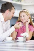 Young couple having tea in a cafeteria - stock photo