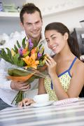 Young man giving a bouquet of flowers to a young girl sitting at a table - stock photo