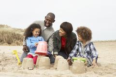 Stock Photo of young family building sandcastle on beach holiday